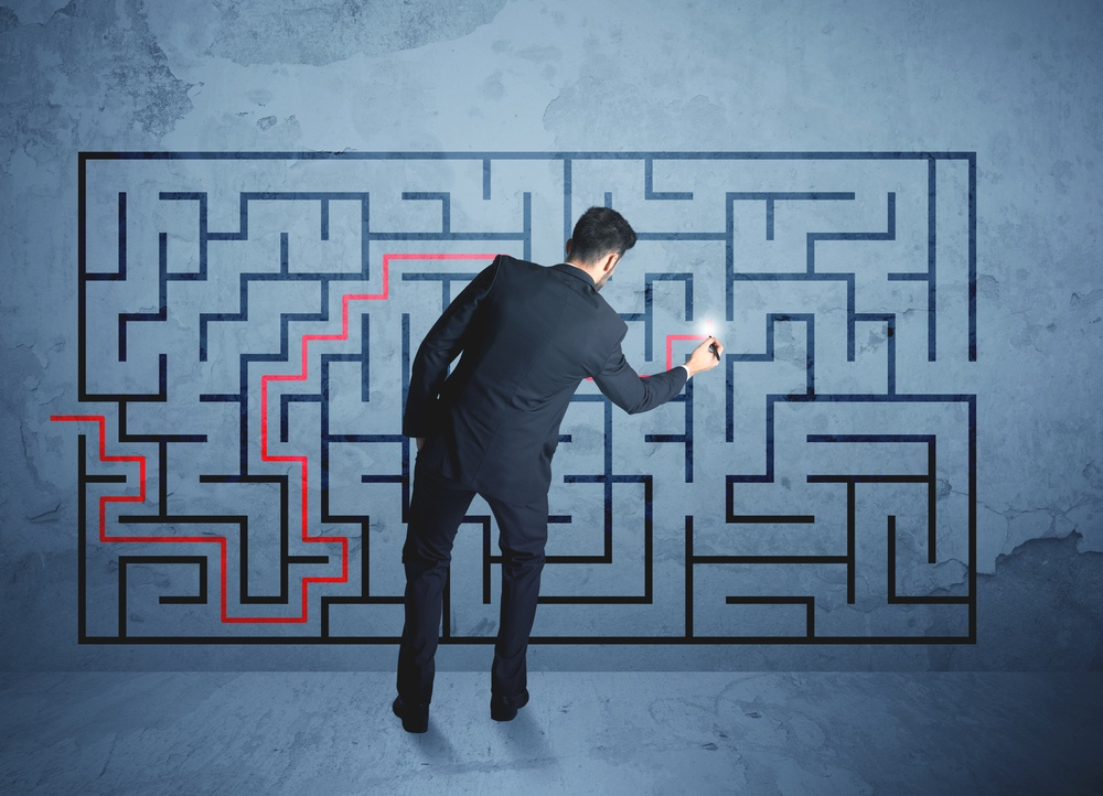 Businessman finding the solution of a maze-1